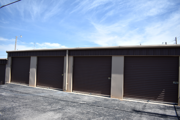 Image of storage units - brown doors and tan building exterior.