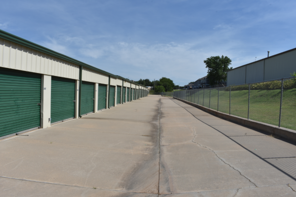 An image of a row of storage units with beige exterior and green, metallic doors.