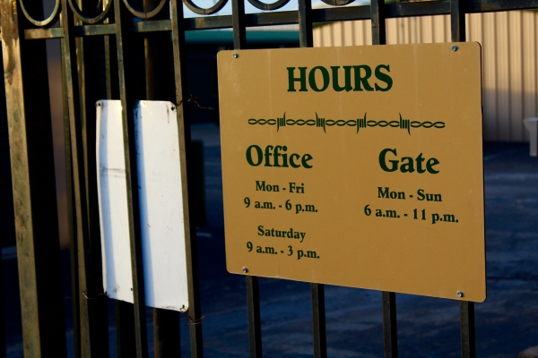 Sign with the facilities hours, office, and gate information.